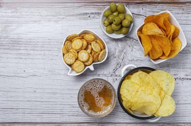 Assortimento di snack a casa con patatine fritte, birra, cracker, olive verdi e nere sulla tavola di legno