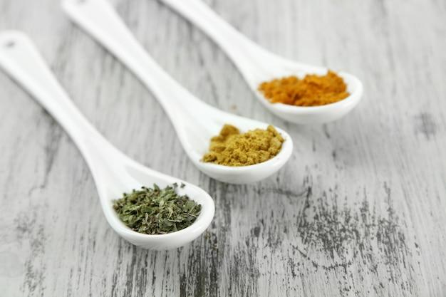 Assortimento di spezie in cucchiai bianchi sul tavolo di legno