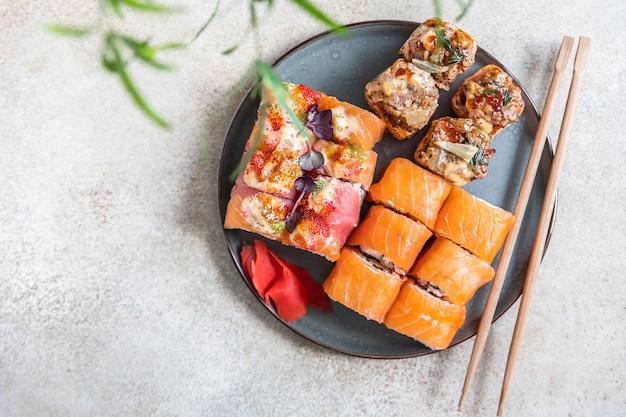 Assortimento di involtini di sushi serviti con bastoncini di zenzero su piatto di ceramica menu di sushi cibo giapponese