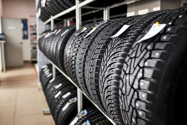 Assortimento di pneumatici per auto in officina, sostituzione di pneumatici invernali ed estivi. concetto di sostituzione stagionale dei pneumatici.