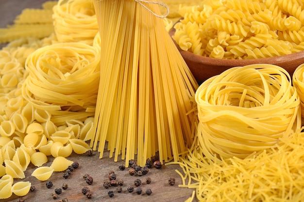 Assortimento di pasta italiana cruda e pepe nero su fondo di legno da vicino