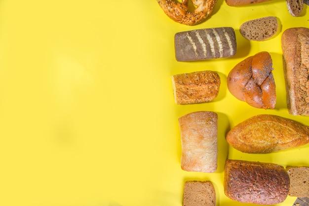 Assortimento di vari deliziosi pane appena sfornato, sulla superficie luminosa alla moda vista dall'alto lo spazio della copia, modello su giallo