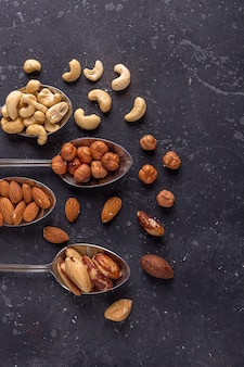 Assortimento di vari tipi di noci: anacardi, nocciole, mandorle, noci del brasile su cucchiai d'argento di metallo su sfondo scuro