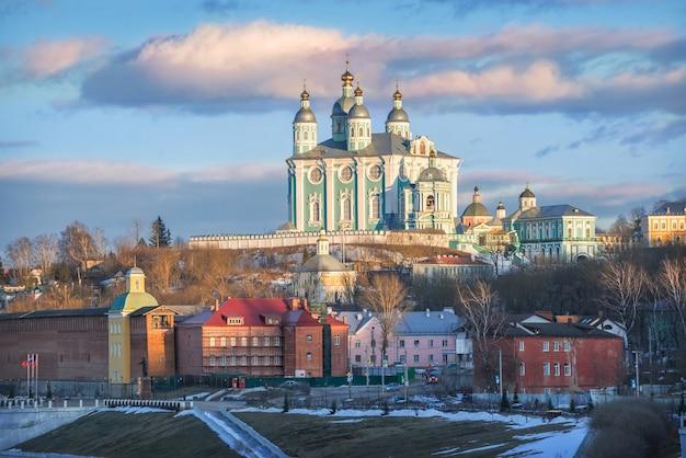 Cattedrale dell'assunzione sulle rive del fiume dnepr a smolensk sotto un cielo blu di primavera al tramonto