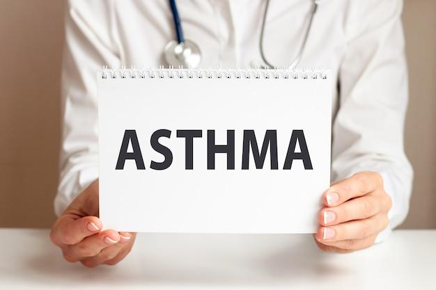 Carta di asma nelle mani del medico. mani del medico un foglio di carta con testo asma, concetto medico.