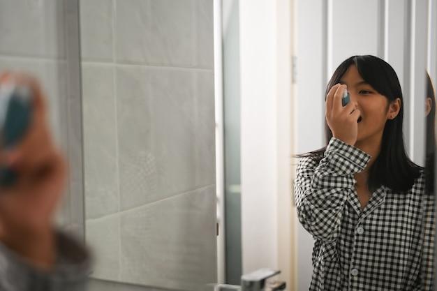Ragazza asmatica che utilizza un inalatore per l'asma durante gli attacchi di asma nella toilette di casa.