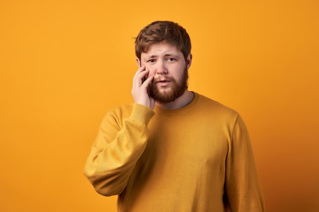 Stupito maschio attraente ha la barba lunga rossa, si meraviglia di notizie improvvise, tiene la bocca leggermente aperta, fissa la telecamera, indossa abiti casual e occhiali, posa contro un muro bianco con uno spazio vuoto