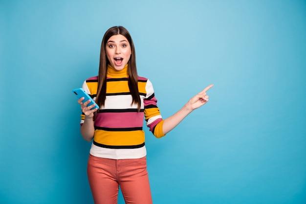 Stupito ragazza pazza punta il dito indice copyspace usa il telefono intelligente indicare pubblicità incredibile promozione urlo impressionato wow omg indossare pantaloni rossi pantaloni maglione isolato muro di colore blu