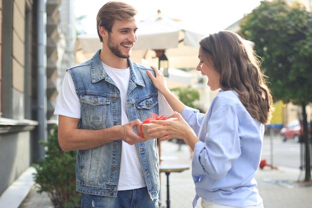 Coppia eccitata stupita in abiti estivi sorridenti e tenendo insieme la scatola presente mentre si trovava sulla strada della città.