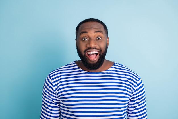 Il ragazzo afroamericano funky stupito guarda vedere incredibili occasioni della stagione estiva del venerdì nero impressionato urlo incredibile inaspettato indossare abito nautico isolato muro di colore blu