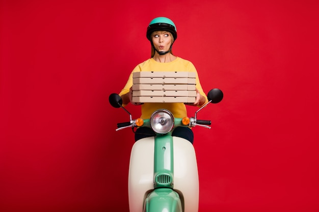 Stupito ragazza bike driver consegna pila pila lato aspetto pizza sulla parete rossa