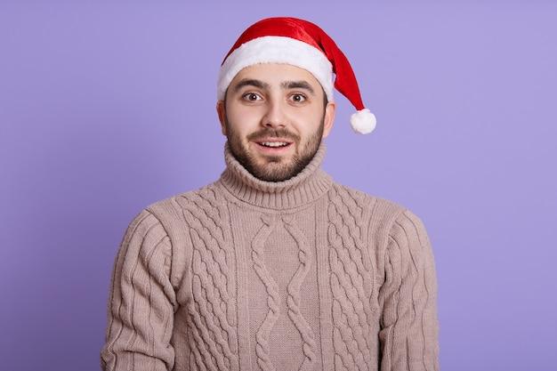 Stupito impressionato giovane barbuto con grandi occhi, che indossa un cappello rosso di babbo natale e un caldo maglione beige su viola
