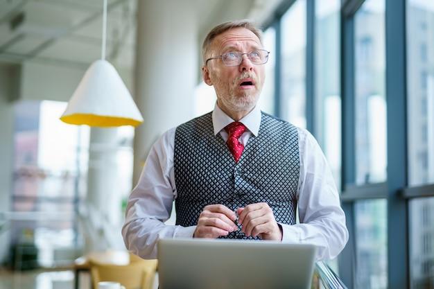 Uomo d'affari senior stupito con la bocca aperta. lavorare con il computer portatile.