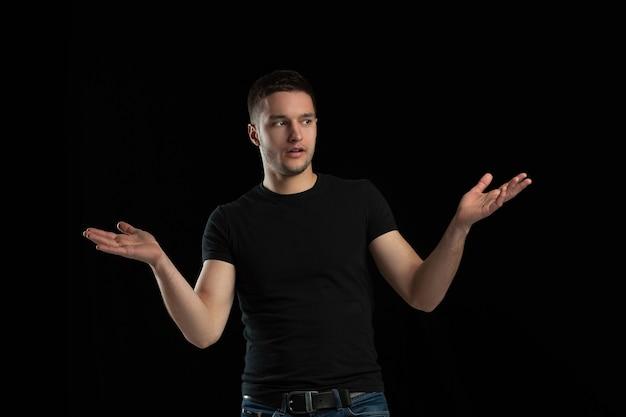Stupito, scioccato. ritratto monocromatico di giovane uomo caucasico isolato sulla parete nera. bellissimo modello maschile. emozioni umane, espressione facciale, vendite, concetto di annuncio. cultura giovanile.