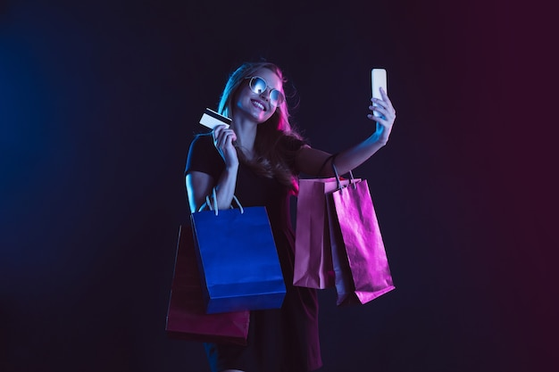 Stupito scioccato dalle borse della spesa allegro ritratto di giovane donna alla luce al neon
