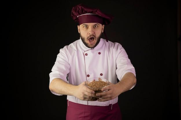 Stupito giovane chef barbuto in uniforme tenendo la ciotola di cereali