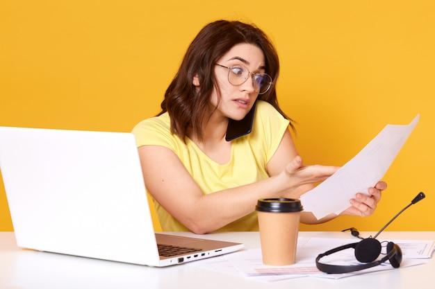 La giovane donna di affari stupita che tiene i documenti in mano e che parla sul telefono cellulare, indossando la maglietta e gli occhiali, ha i capelli scuri