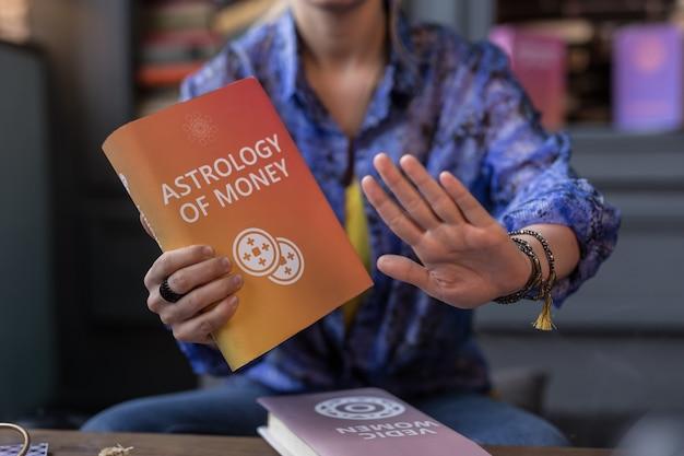 Astrologia e denaro. messa a fuoco selettiva di un libro sull'astrologia in mani femminili