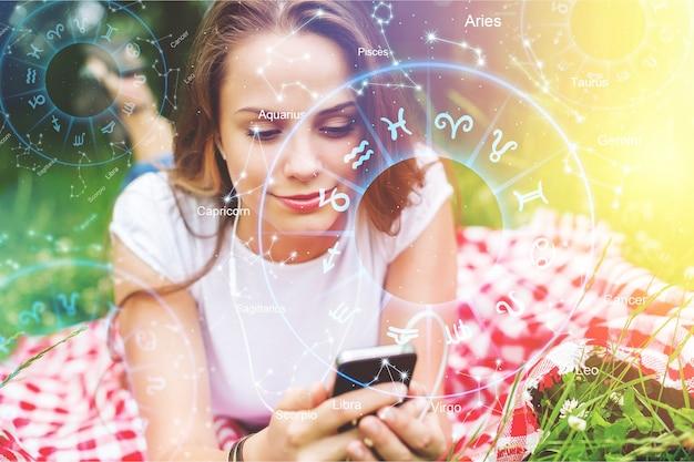 Concetto di app per smartphone astrologia, donna che utilizza il telefono cellulare, primo piano delle mani - immagine