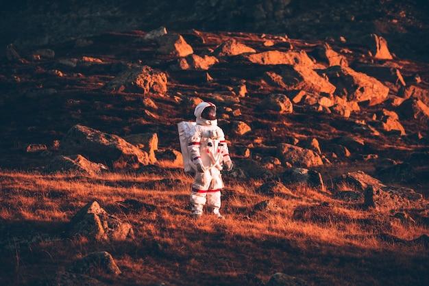 Astronauta che esplora un nuovo pianeta. alla ricerca di una nuova casa per l'umanità. concetto di scienza e natura
