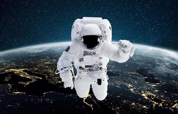 L'astronauta vola nello spazio esterno contro il pianeta terra notturno con la luce della città
