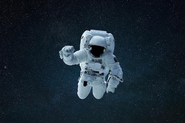 Astronauta nello spazio esterno. l'uomo spaziale galleggia nello spazio con le stelle. concetto di missione spaziale