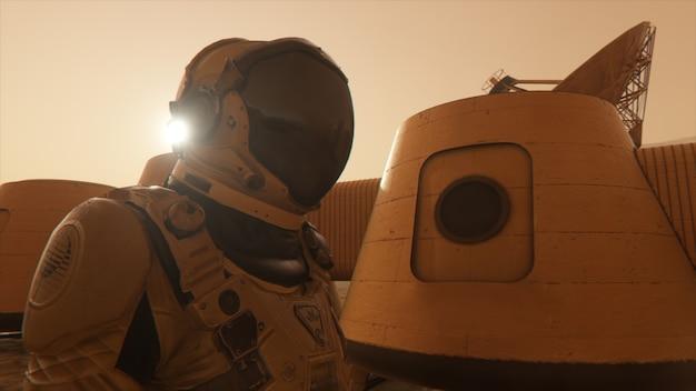 Astronauta sul pianeta marte, facendo una deviazione intorno alla sua base. astronauta che cammina lungo la base.