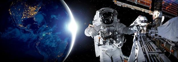 L'astronauta astronauta fa la passeggiata nello spazio mentre lavora per la stazione spaziale
