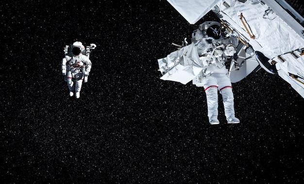 Gli astronauti astronauti fanno una passeggiata nello spazio mentre lavorano per la stazione spaziale