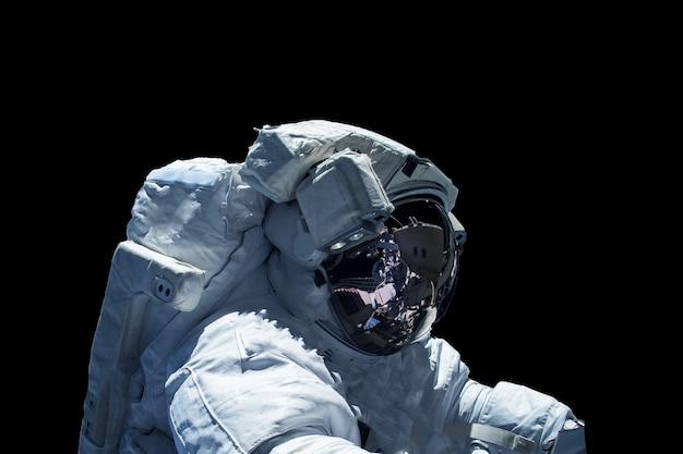 Astronauta in una tuta spaziale isolata su uno sfondo nero. gli elementi di questa immagine sono stati forniti dalla nasa. foto di alta qualità