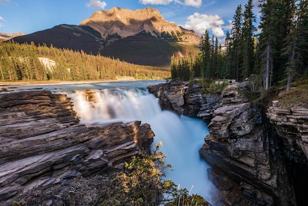 Athabasca falls con la montagna sullo sfondo che è gialla dal sole al tramonto