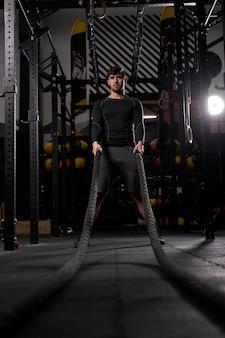 Atleta che fa esercizio di corde di battaglia in palestra cross fit. motivazione sport concept. maschio impegnato in un intenso allenamento piove. copia spazio.