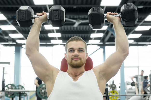 Atleta che fa esercizio per le spalle con manubri seduto su una panchina. giovane uomo muscoloso si allena in palestra.