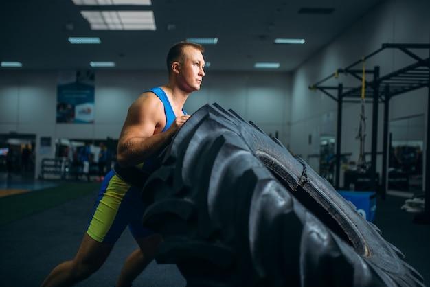 Atleta che fa esercizio con pneumatici per camion, crossfit