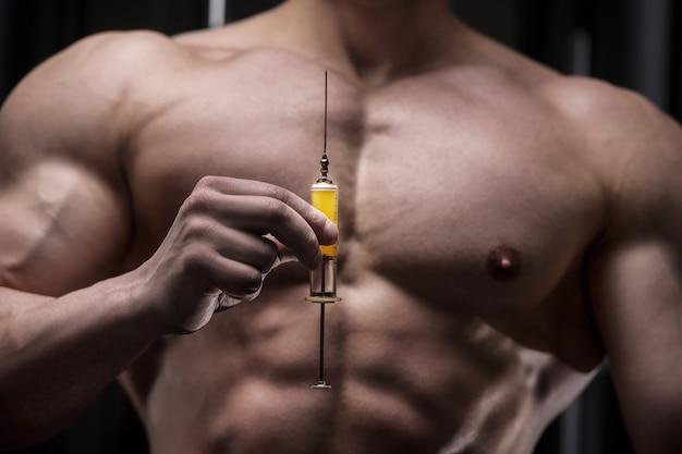 L'atleta tiene una siringa, iniettore davanti a lui con un torso nudo. concetto di medicina dello sport e della vaccinazione