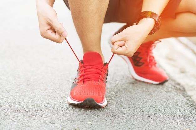 Mani maschii dell'atleta che legano i lacci delle scarpe da corsa prima dell'allenamento. runner si prepara per l'allenamento. concetto di stile di vita attivo di sport.