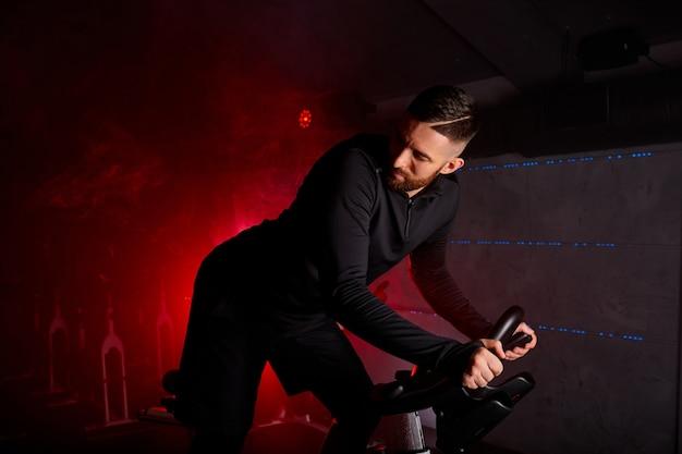 Atleta maschio si sta allenando in bici in palestra, guardando indietro, alla concorrenza. in uno spazio fumoso illuminato al neon rosso