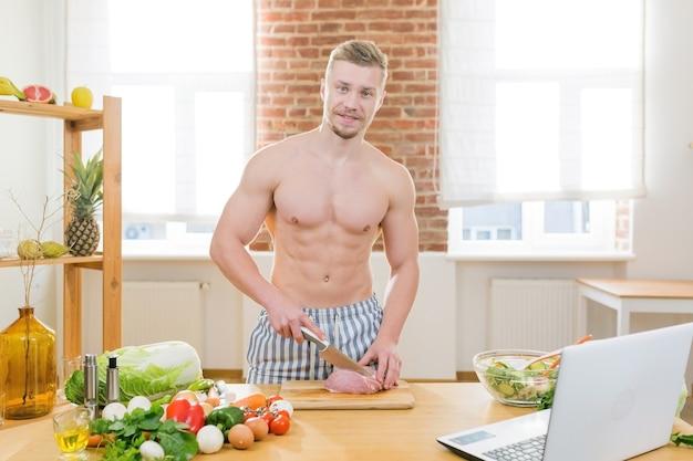 L'atleta cucina in cucina, usa verdure e carni varie per cucinare la cena, guarda corsi di cucina online