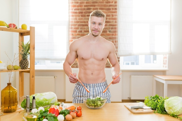 L'uomo atleta cucina in cucina, usa verdure e carni varie per cucinare la cena