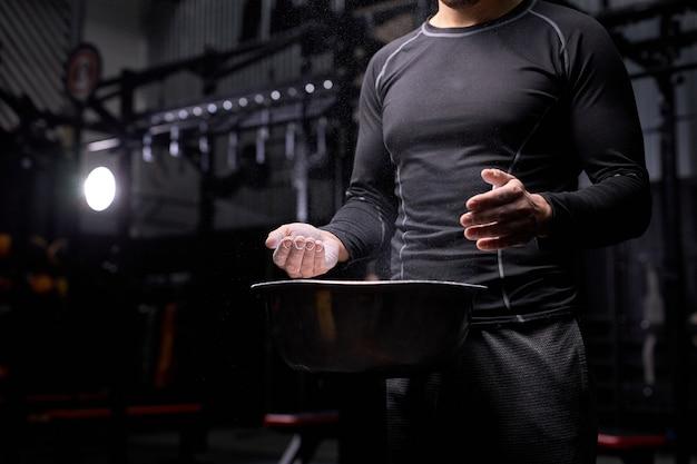 Uomo dell'atleta che si prepara per l'allenamento di sollevamento pesi, utilizzando talco, preparando le mani per l'allenamento. in palestra. concetto di sport e bodybuilding