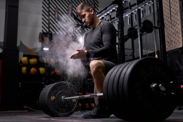 L'atleta si sta preparando per l'allenamento cross fit. cnfident powerlifter usa talco preparandosi a sollevare pesi elevati. alla moderna palestra, centro fitness