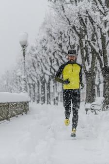 Uomo dell'atleta corre su un marciapiede della città durante forti nevicate
