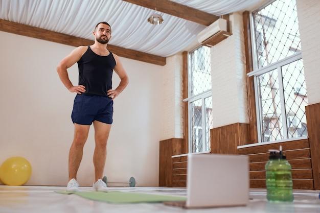 Uomo atleta si allena duramente in palestra vuota o in piedi a casa davanti al computer portatile. riscaldamento del giovane auto isolato e motivato facendo esercizi speciali per i muscoli. allenati durante il blocco del coronavirus.