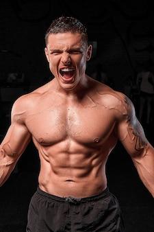 Atleta muscoloso bodybuilder brutale emotivo in posa in palestra. lo sfondo è nero