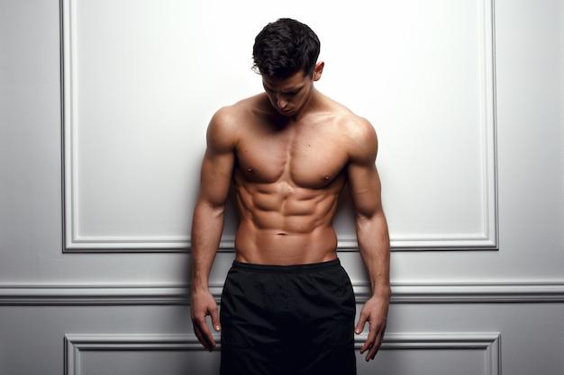 Atleta, muscoloso uomo al muro bianco pone senza camicia, mostrando addominali scolpiti, sfondo bianco.