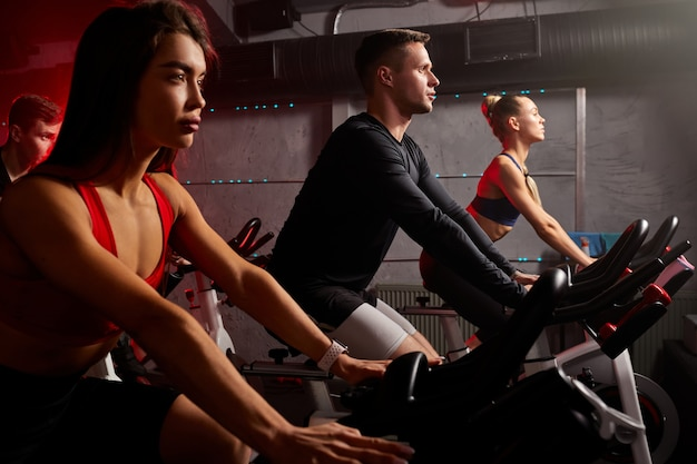 Persone di atleta che si esercitano e si allenano in palestra, bicicletta da bicicletta, tuta da ginnastica. allenamento, salute, benessere nel fitness