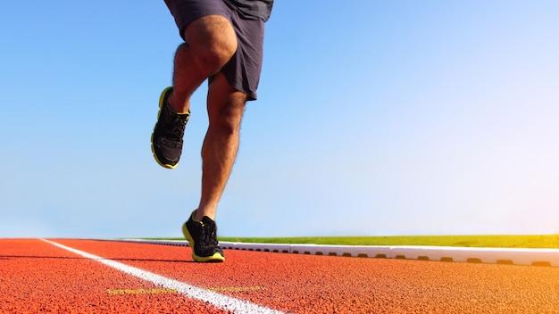 Piedi del corridore dell'atleta che corrono sulla pista da corsa. sfondo di sport