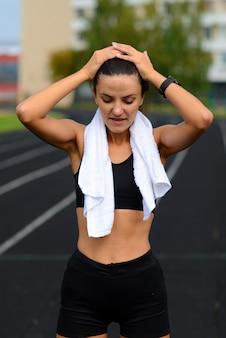 Corridore dell'atleta che corre sulla pista di atletica che prepara il suo cardio. donna che pareggia per la gara allo stadio all'aperto estivo.