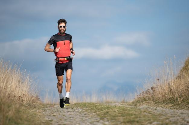 Un corridore di atleta con la barba si allena su una strada di montagna