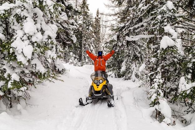 Atleta su una motoslitta che si muove nella foresta invernale
